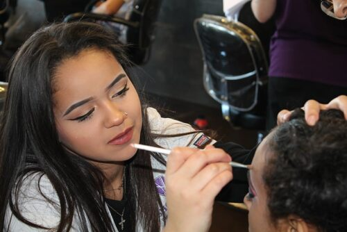 Shore cosmetology student applying makeup to client